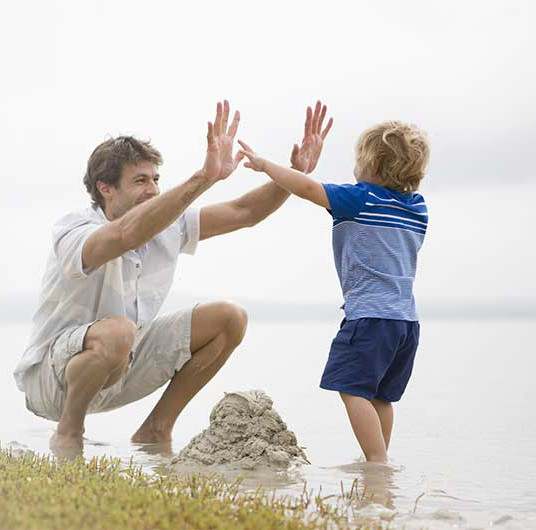 dad-child-hi-five-over-mud-castle-small